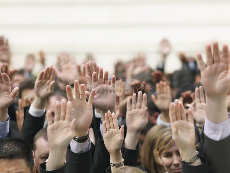 Geschäfts-Menge, die Hände anhebt lizenzfreies stockfoto