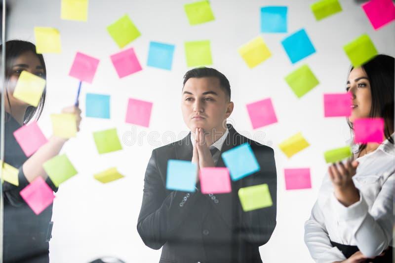 Geschäfts-, Start-, Planungs-, Management- und Leutekonzept - glückliches kreatives Team mit Aufklebern auf Büroglasbrett stockfotografie