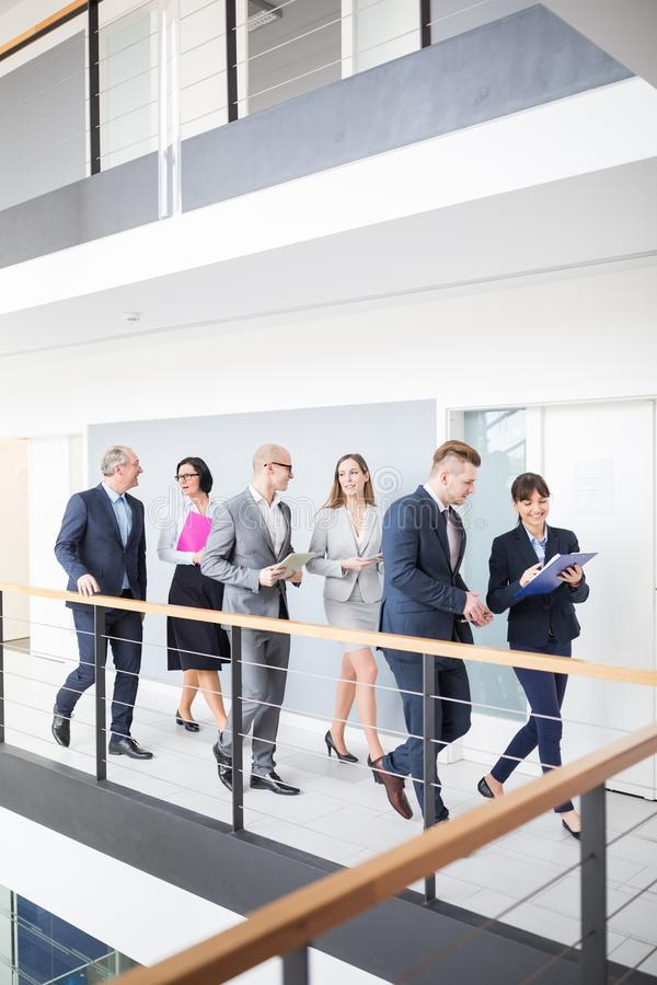 Geschäfts-Team Discussing While Walking On-Korridor im Büro stockfotografie
