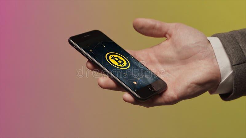 Geschäfts-, Technologie- und cryptocurrencykonzept - nah oben von der männlichen Hand, die Smartphone hält und intelligente Uhr m lizenzfreie stockfotografie