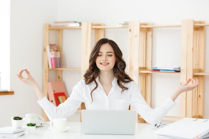Geschäfts-und Gesundheits-Konzept: Junge Frau des Porträts nahe dem Laptop, übende Meditation am Schreibtisch, vor stockfotos