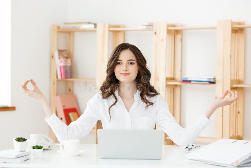 Geschäfts-und Gesundheits-Konzept: Junge Frau des Porträts nahe dem Laptop, übende Meditation am Schreibtisch, vor stockbilder