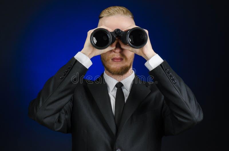 Geschäfts- und Suchthema: Bemannen Sie im schwarzen Anzug, der schwarze Ferngläser auf einem dunkelblauen Hintergrund im lokalisi stockbilder