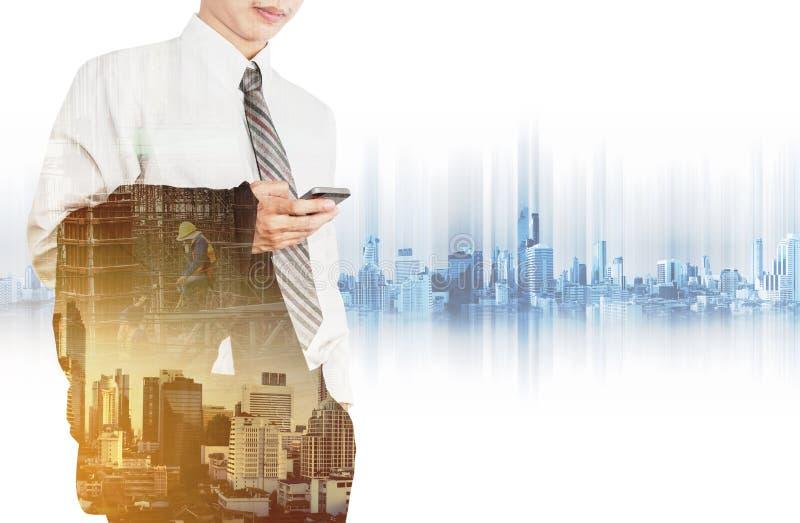 Geschäftsangestellter, der intelligentes Telefon mit Doppelbelichtungsstadt im Sonnenaufgang und Standortbau mit Arbeitskräften v lizenzfreie stockbilder