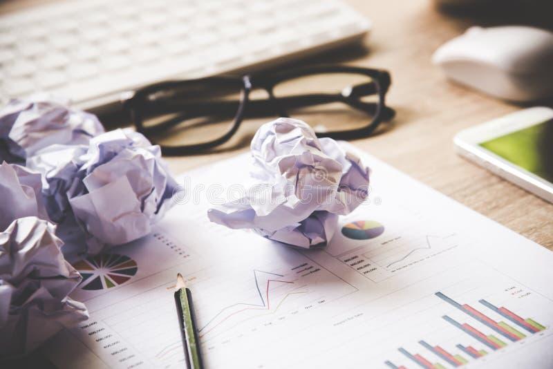 Geschäftsarbeitsplatz mit Tastaturmaus und zerknitterten Papierbällen, Papiere mit Diagrammen und Diagramme lizenzfreie stockfotografie