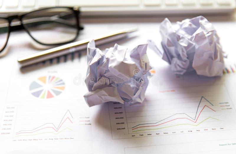 Geschäftsarbeitsplatz mit Tastaturmaus und zerknitterten Papierbällen, Papiere mit Diagrammen und Diagramme, stockfotos
