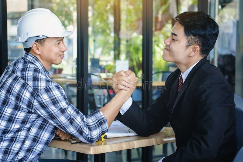 Geschäftsarchitekten sind junge und Energieherausforderung durch Arm-wre lizenzfreie stockbilder