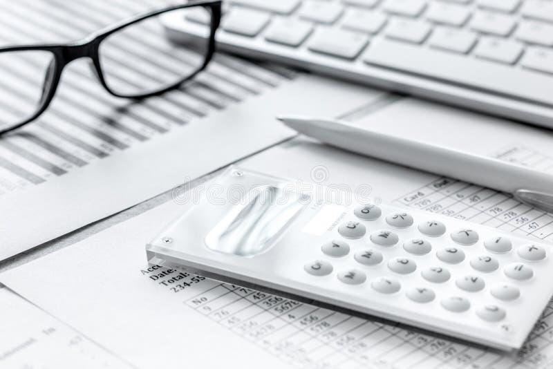 Geschäftsbericht, der mit Taschenrechner und Gläsern auf Bürohintergrund sich vorbereitet stockfotos