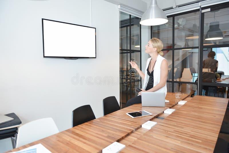 Geschäftsblondine, die mit leerem Bildschirm im Büro fernsehen stockfotografie