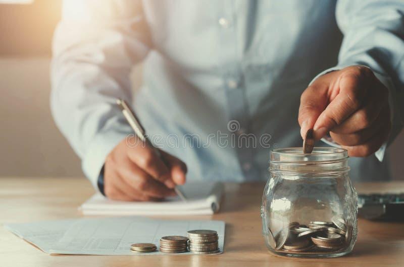Geschäftsbuchhaltung mit Einsparungsgeld mit der Hand, die herein Münzen setzt stockfotografie