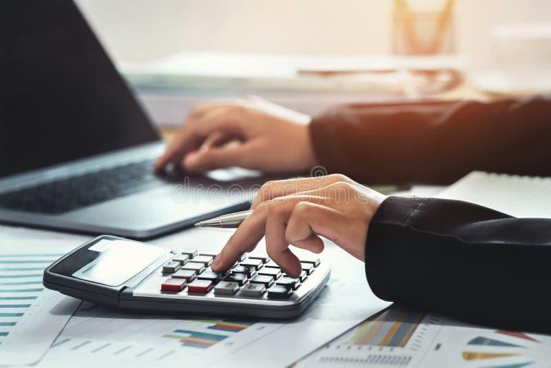 Geschäftsbuchhaltungsfinanzkonzept der Buchhalter, der Taschenrechner für verwendet, berechnen mit Laptopfunktion im Büro stockbilder