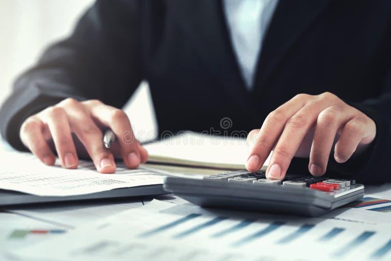 Geschäftsbuchhaltungsfinanzkonzept der Buchhalter, der Taschenrechner für verwendet, berechnen mit Laptopfunktion im Büro lizenzfreie stockfotos
