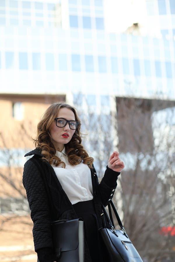 Geschäftsdame in der strengen Kleidung auf dem Hintergrund von Gebäuden lizenzfreie stockfotografie