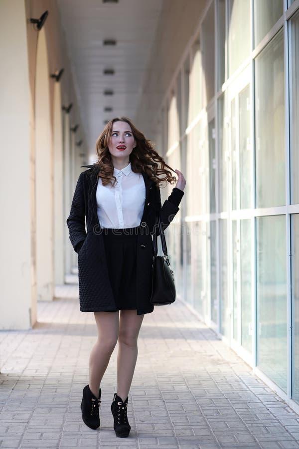 Geschäftsdame in der strengen Kleidung auf dem Hintergrund von Gebäuden stockfotografie