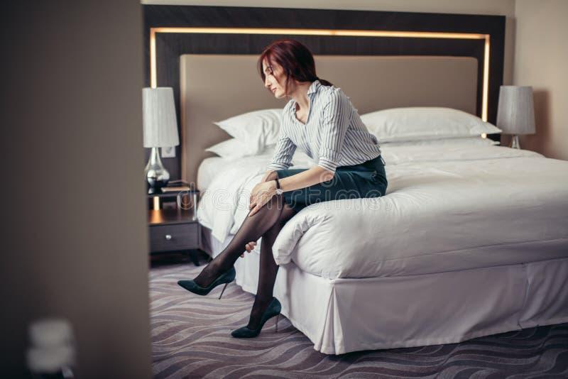Geschäftsdame, die nach einer langen Reise stillsteht auf Bett im Hotelzimmer ermüdet ist stockfotos
