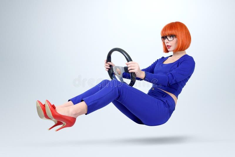 Geschäftsdame im blauen Fahrerauto mit einem Rad, Frau, die Konzept fährt lizenzfreie stockbilder