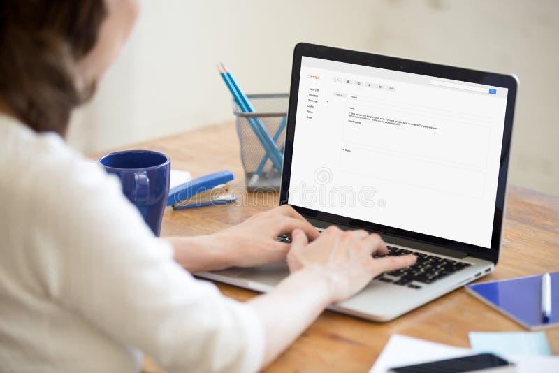 Geschäftsdame in Schreibenantwort des Büros auf Unternehmens-E-Mail stockbild