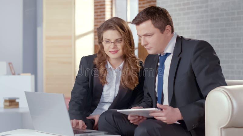 Geschäftsdame und -mann, die Darstellung auf Laptop überprüfen, arbeiten im Geschäft zusammen lizenzfreie stockbilder