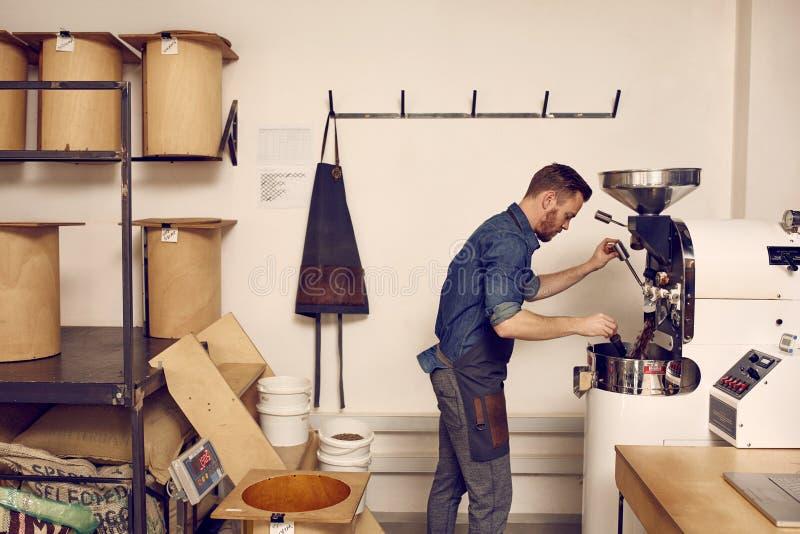 Geschäftseigentümer, der eine moderne Kaffeebohne-Bratmaschine betreibt stockfotos