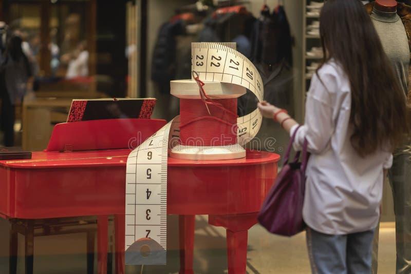 Geschäftsfenster, Anzeigenhandelsausrüstung, dekorative Nähnadel und Spule mit rotem Faden Gehendes und schauendes Mädchen stockfotografie