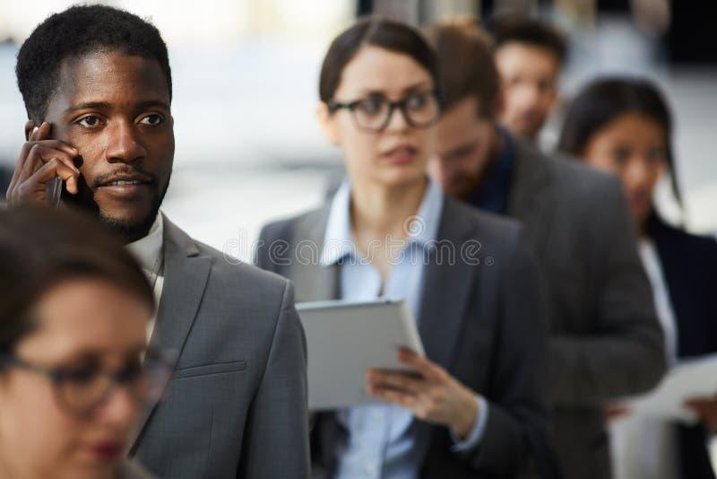 Geschäftsforumteilnehmer, die auf Ausrichtung in der Linie warten lizenzfreies stockbild
