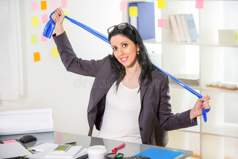 Geschäftsfrauübung in ihrem Büro mit dem Streifenausdehnen lizenzfreie stockbilder