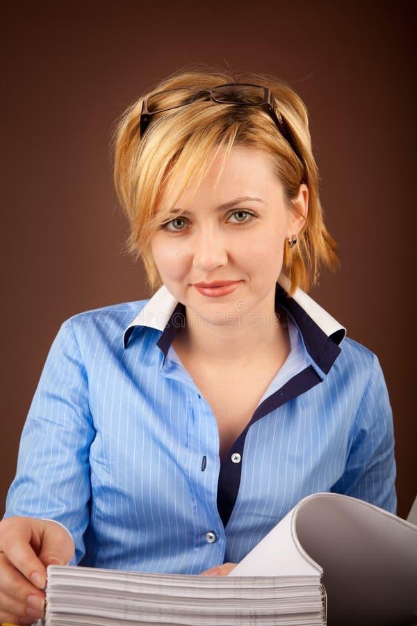 Geschäftsfrau überprüft die Dokumente in einem Faltblatt lizenzfreie stockfotografie