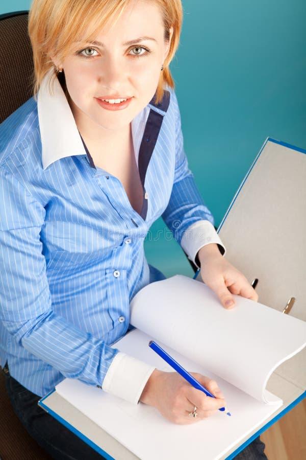 Geschäftsfrau überprüft die Dokumente in einem Faltblatt stockbild