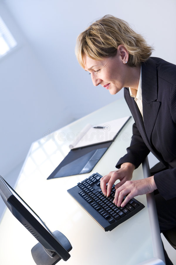 Geschäftsfrau auf Computer lizenzfreie stockfotografie