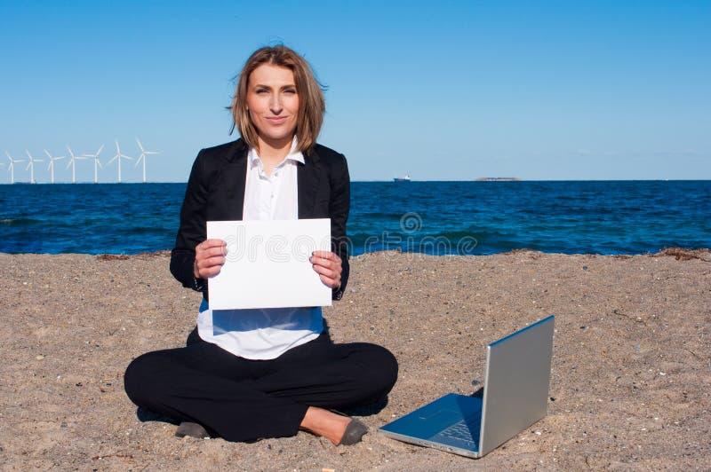 Geschäftsfrau auf dem Sand mit Laptop, copyspace stockbild