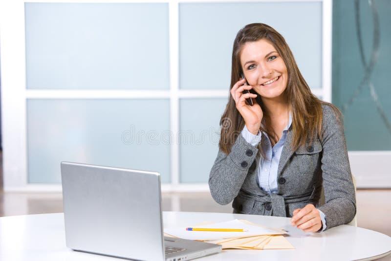 Geschäftsfrau auf einem Handy und einem Laptop lizenzfreie stockfotografie