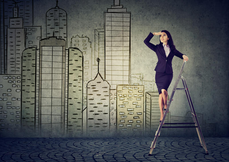 Geschäftsfrau auf einer Leiter, die weit weg schaut, prognostizierend Immobilienmarkt stockfoto