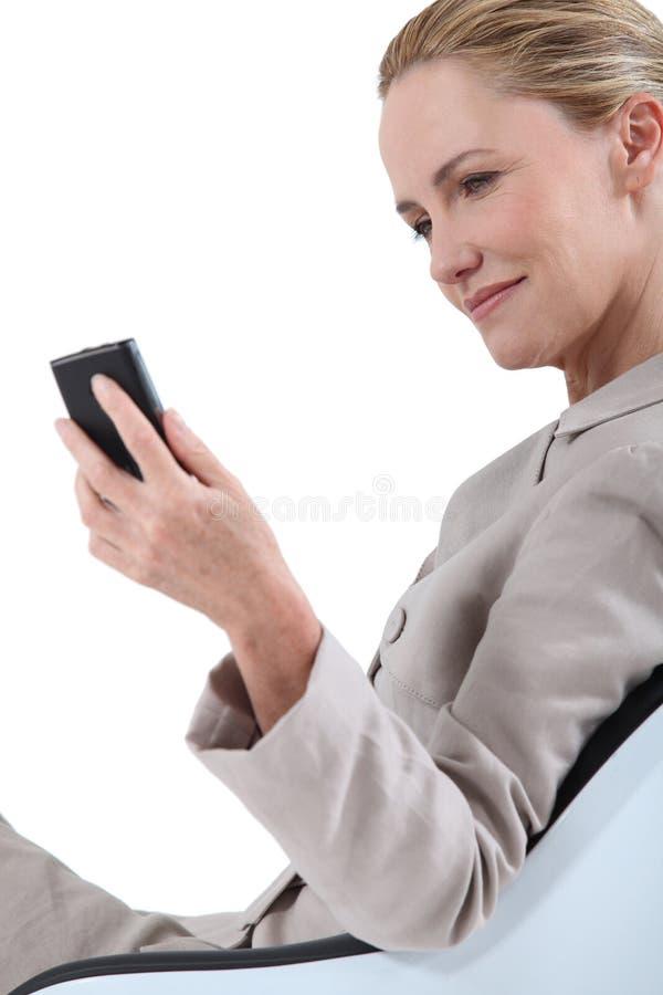 Geschäftsfrau auf Stuhl mit Laptop lizenzfreie stockfotos