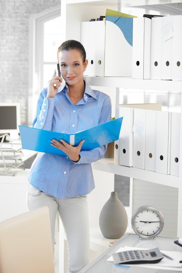 Geschäftsfrau auf Telefonaufruf-Holdingfaltblatt lizenzfreies stockbild
