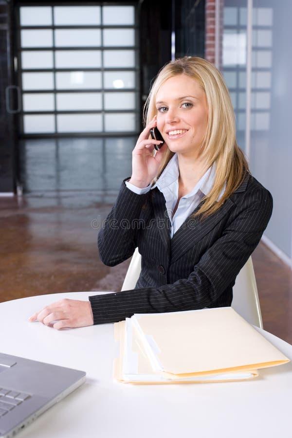 Geschäftsfrau auf Zelle am Schreibtisch lizenzfreie stockfotos