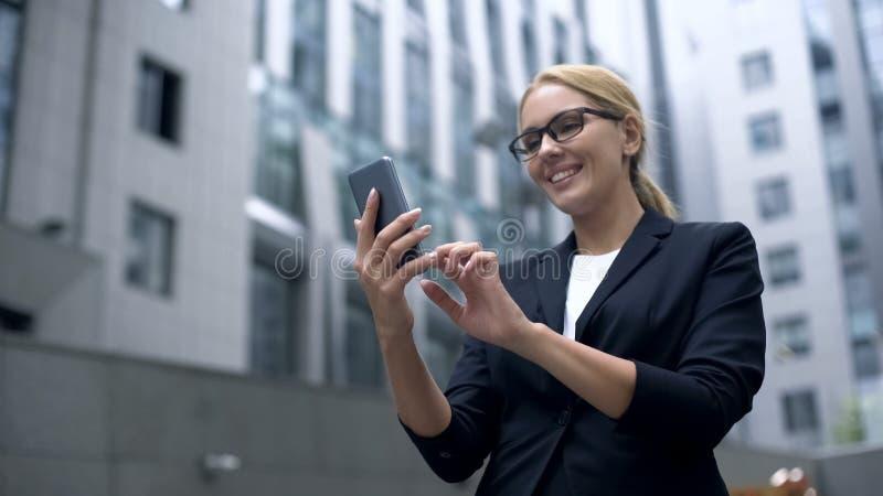 Geschäftsfrau aufgeregt mit bequemer APP im Smartphone, elektronischer Organisator lizenzfreies stockfoto