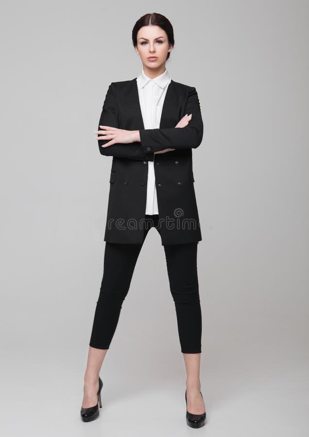 Geschäftsfrau-Büromodemädchen im schwarzen Anzug stockfotografie