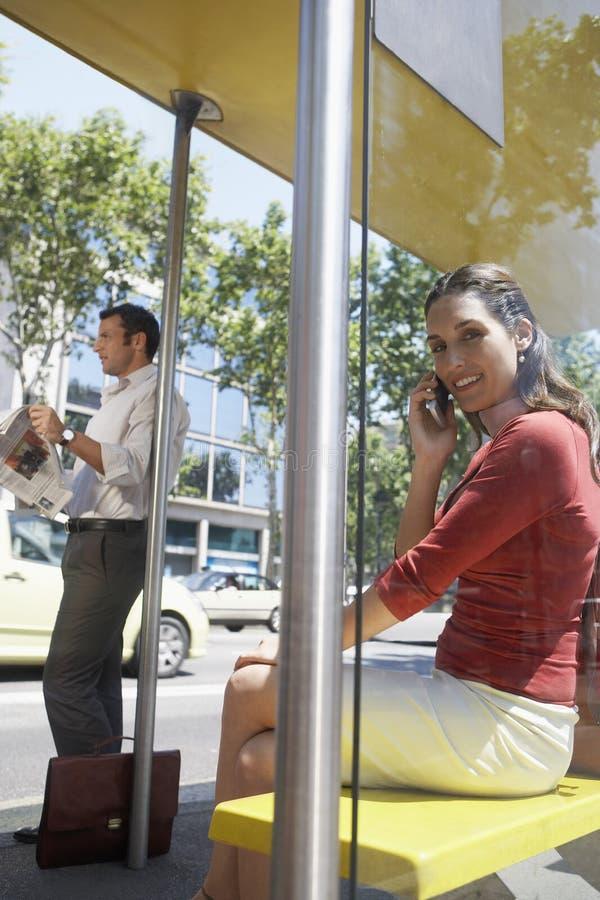 Geschäftsfrau bei einem Anruf an der Bushaltestelle stockfotografie