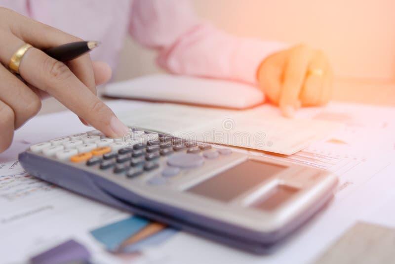 Geschäftsfrau berechnen über Kosten und Diagramme berichten über Tabelle, Taschenrechner auf Schreibtisch der Finanzplanierung Ge lizenzfreie stockfotos