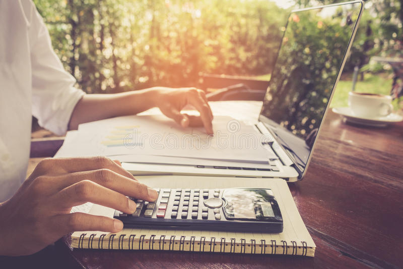 Geschäftsfrau berechnen und das Diagrammdokument analysierend, das mit Laptopweinleseton finanziell ist lizenzfreie stockfotos