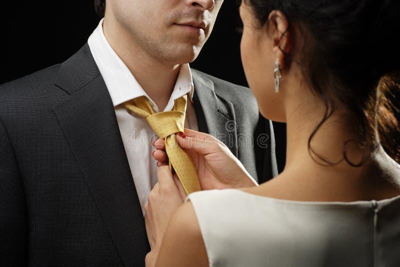 Geschäftsfrau bindet eine Krawatte an einem Geschäftsmann stockfoto
