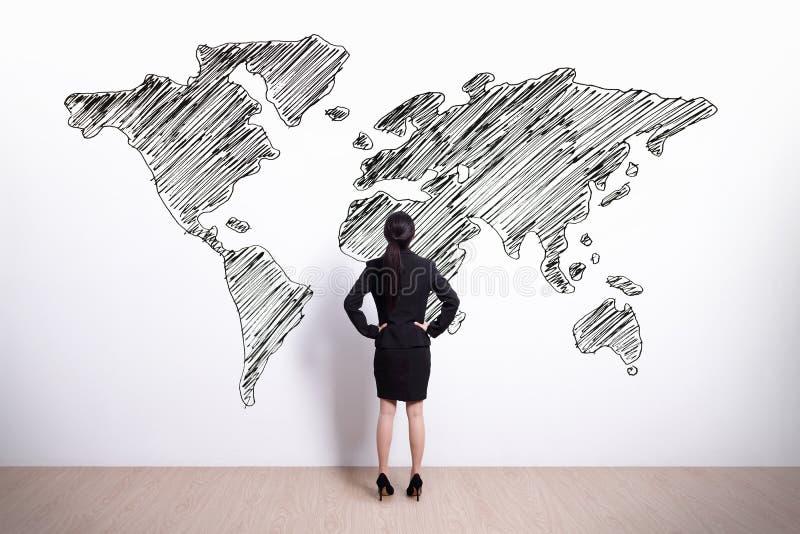 Geschäftsfrau-Blickweltkarte lizenzfreie stockbilder