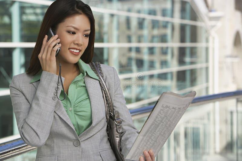 Geschäftsfrau-On Call Reading-Zeitung lizenzfreie stockbilder