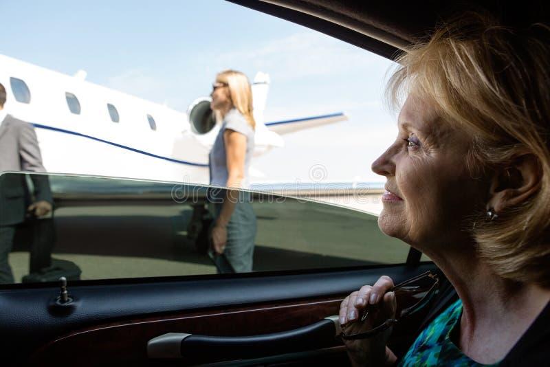 Geschäftsfrau In Car Looking am Privatjet stockfotografie