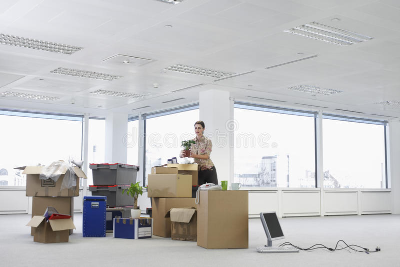 Geschäftsfrau With Cartons Moving in neues Büro lizenzfreie stockfotos