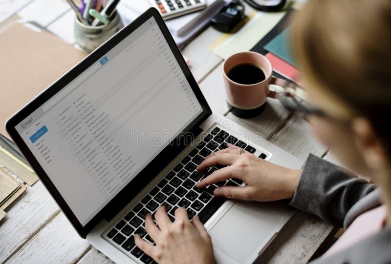 Geschäftsfrau-Checking-E-Mail online auf Laptop stockfotos
