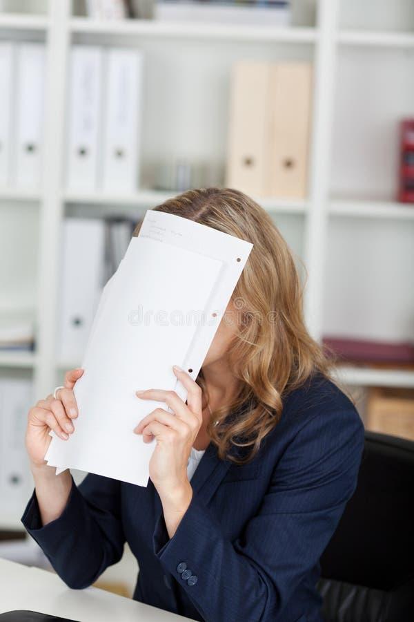 Geschäftsfrau-Covering Face With-Dokumente am Schreibtisch lizenzfreie stockfotografie
