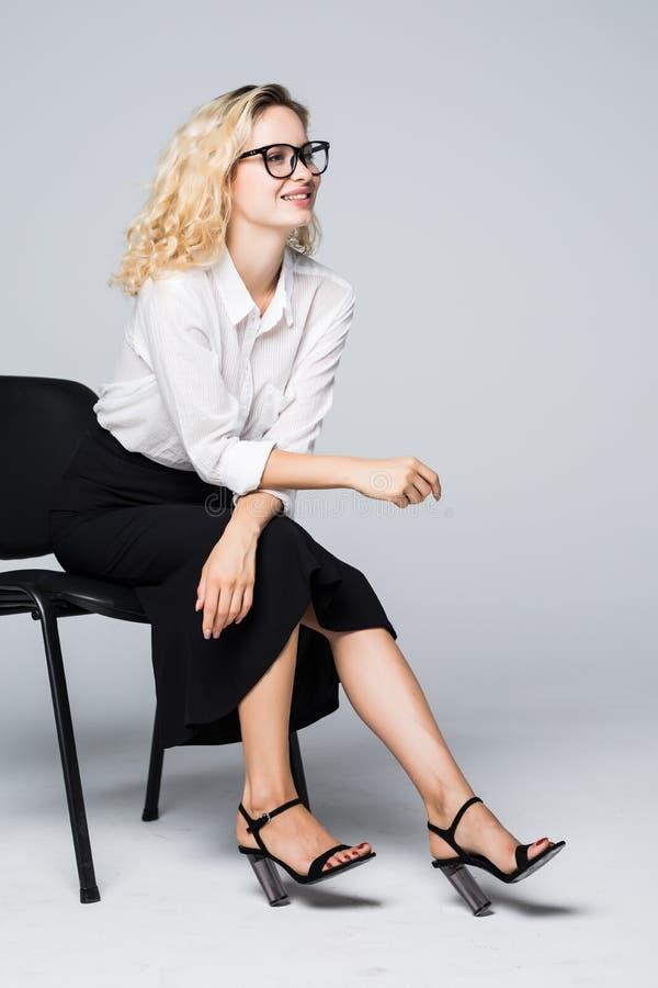 Geschäftsfrau in den Gläsern, die auf einem Stuhl lokalisiert auf weißem Hintergrund sitzen stockbilder