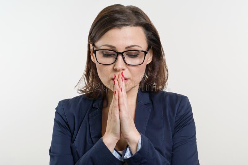 Geschäftsfrau in den Gläsern, geschlossen ihren Augen und betet, meditiert lizenzfreie stockfotos