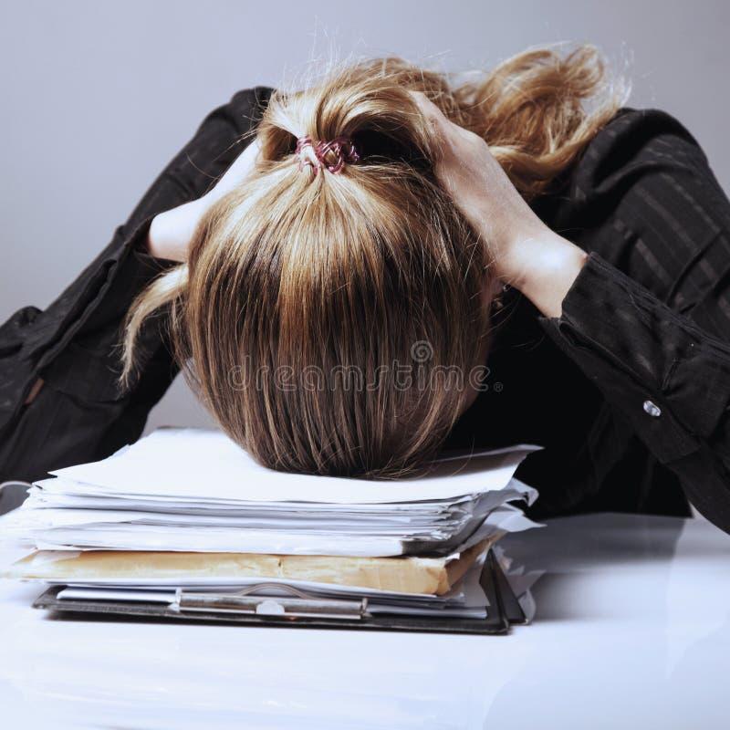 Geschäftsfrau in den Problemen Alleinarbeiten im Büro mit vielem lizenzfreie stockbilder